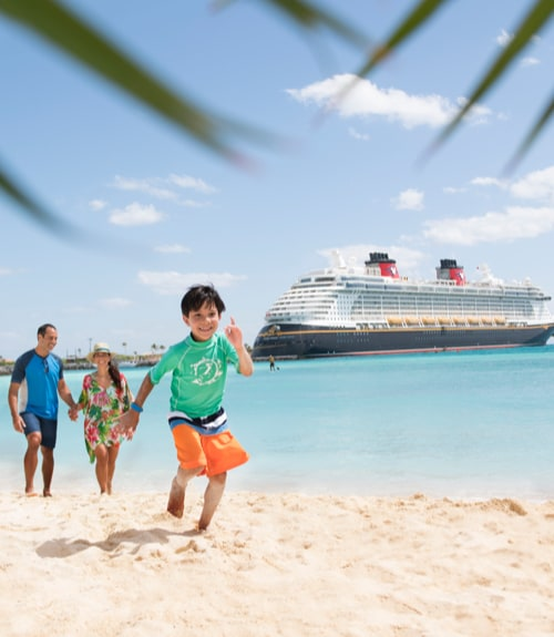 Family on beach with Disney Cruise line in the background
