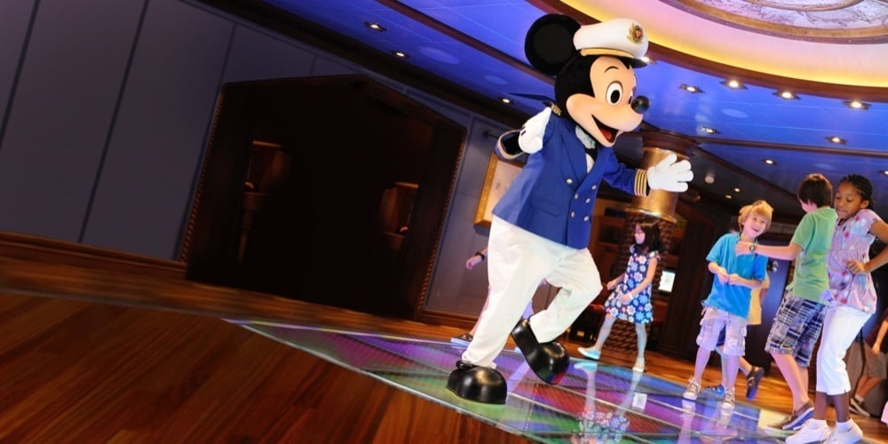 Mickey Mouse, dressed as a sailor dancing with children on a dancefloor