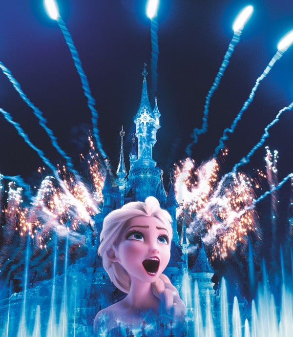 Elsa singing with Sleeping Beauty's castle in the background at night, lit up with frozen colours with fireworks in the background