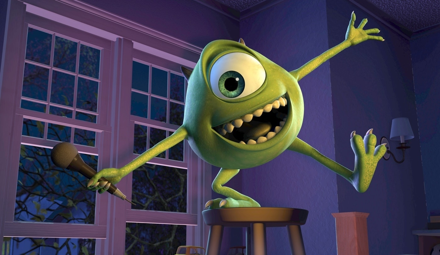 Mike Wazowski posing with a mic while standing on a stool