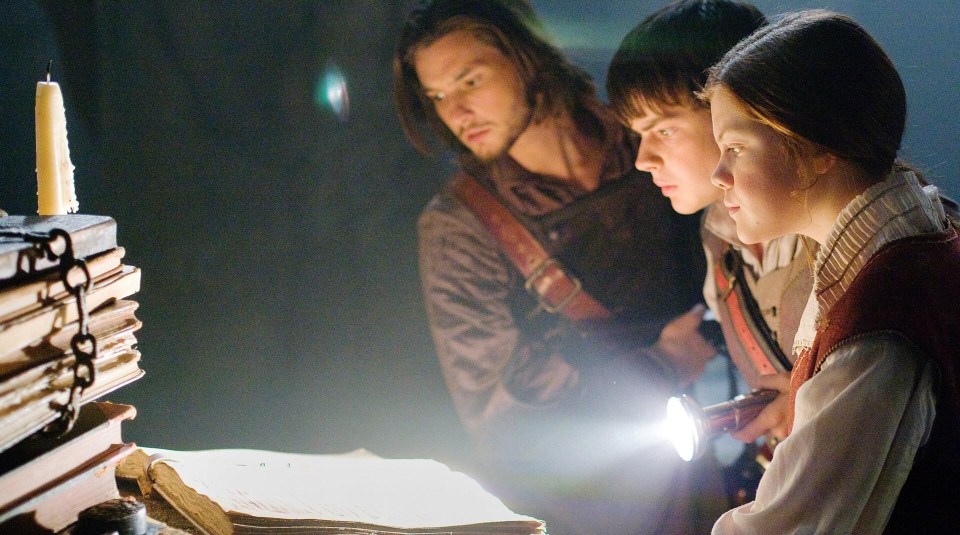 Los personajes de Las crónicas de Narnia observan un libro