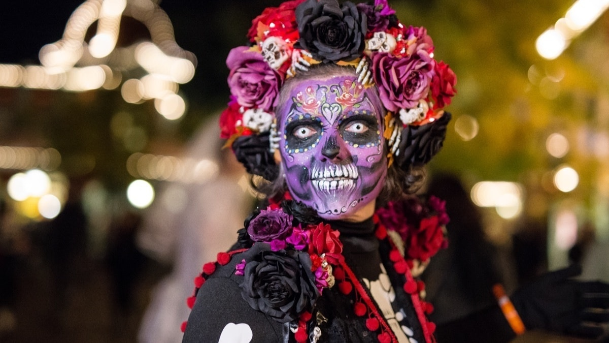 Woman with skeleton face paint with flowers in her hair