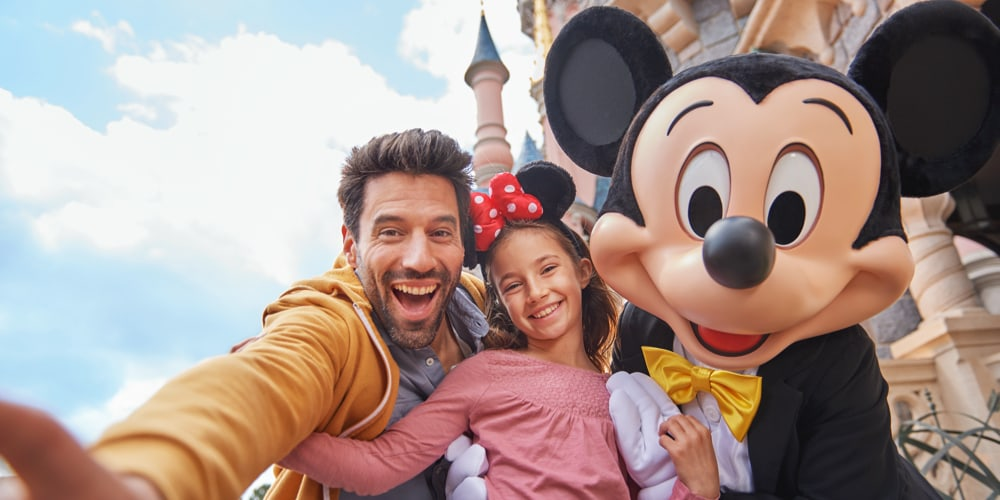 A father and Daughter taking a selfie with Mickey Mouse