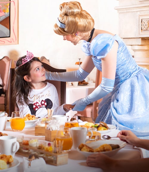 A child wearing a tiara at breakfast with Cinderella