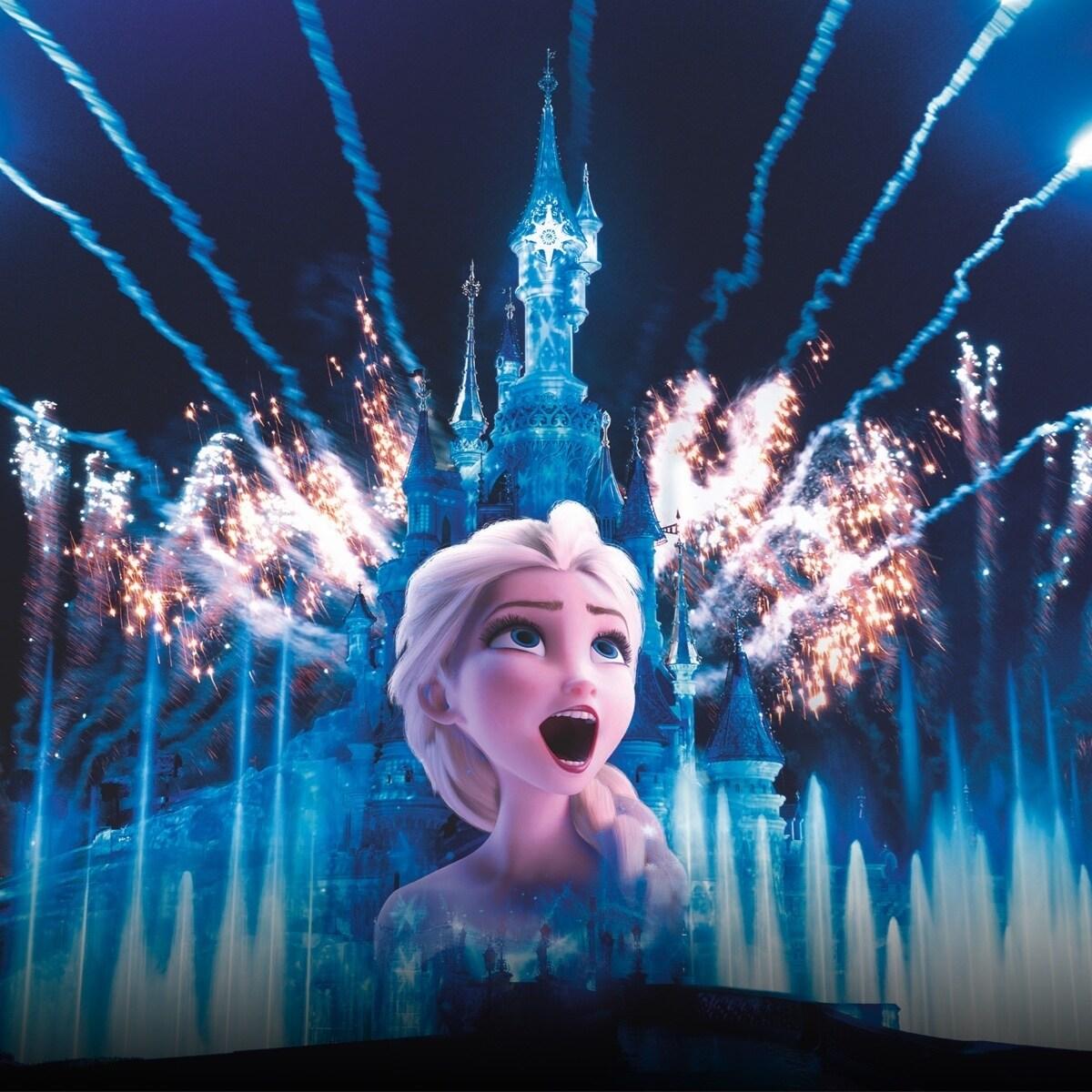Elsa dans son numéro de chant, avec le château de La Belle au Bois Dormant de nuit en arrière-plan, éclairé par un feu d'artifice