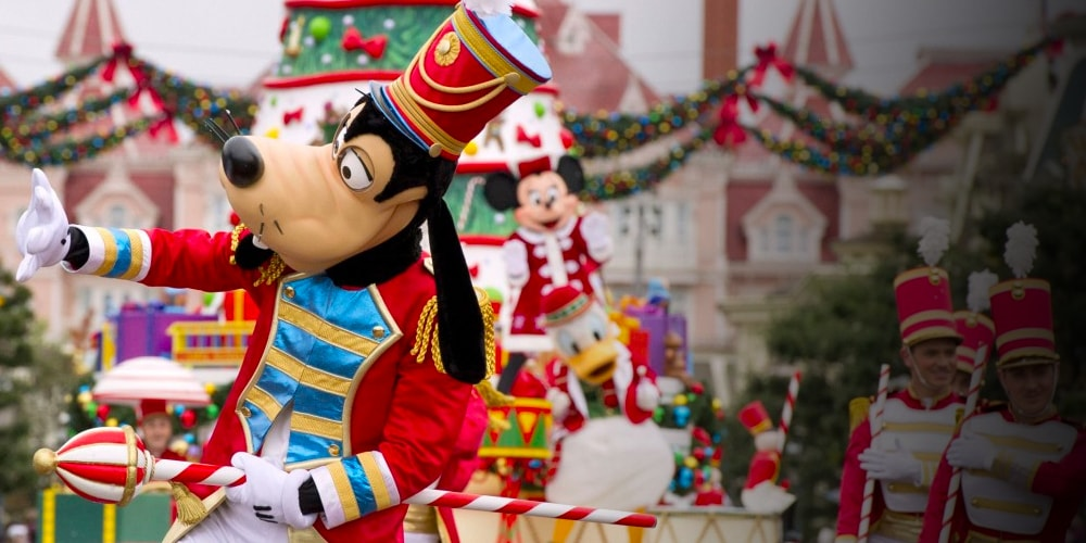 Goofy leading the parade in his carnival outfit with Mickey Mouse and Minnie Mouse on a float in the background in the background