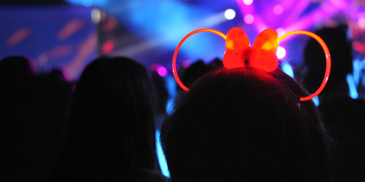 Woman wearing a neon Minnie ears headband