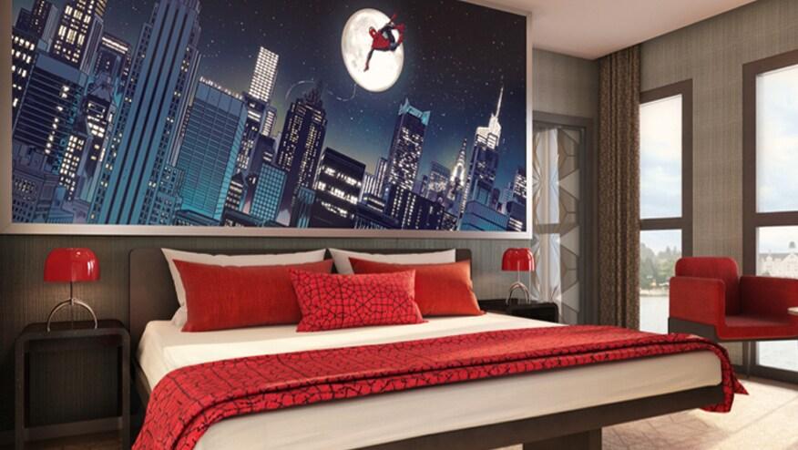 Une chambre dans un hôtel Marvel, avec une image de Spider-Man se balançant dans les airs la nuit au-dessus d'un lit rouge