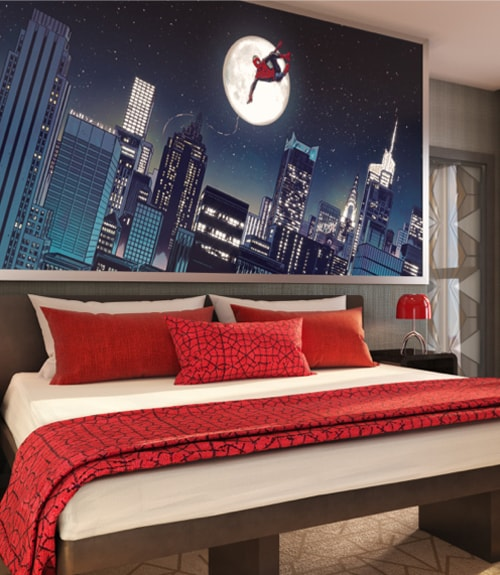 A room in the Marvel hotel with an image of Spiderman swinging at night above the red themed bed
