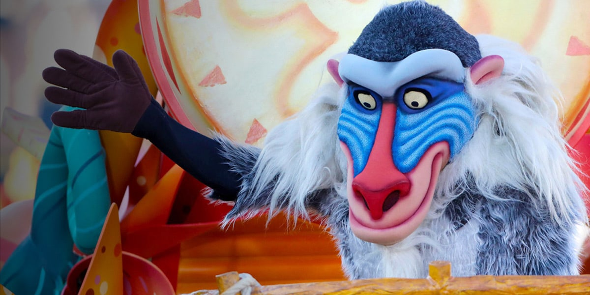 Rafiki with one hand raised while on a Lion King parade float