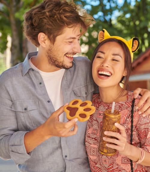 Couple Holding a Lion King cookie and cup wearing Lion King ears
