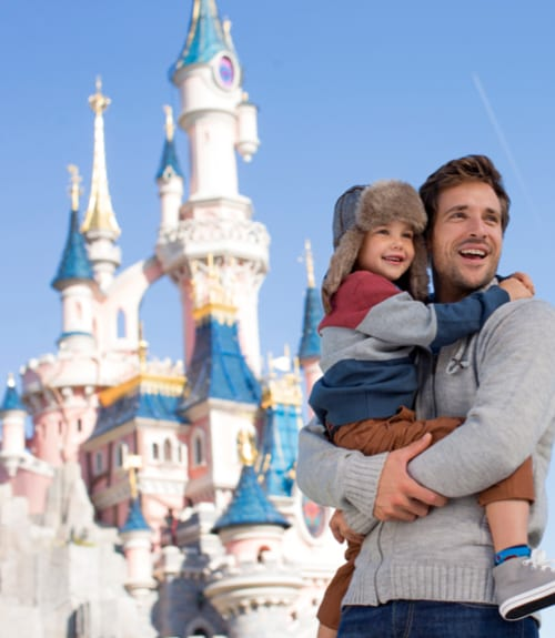 A father laughing with his son outside Sleeping Beauty's castle