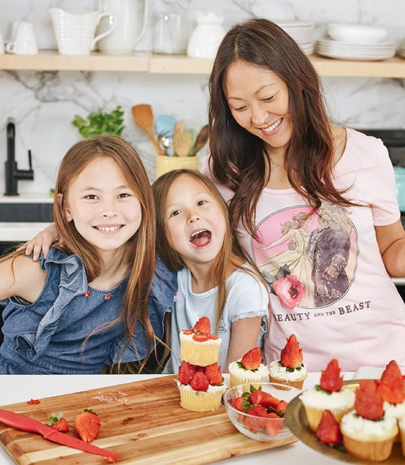 A mother and her daughters making cakes