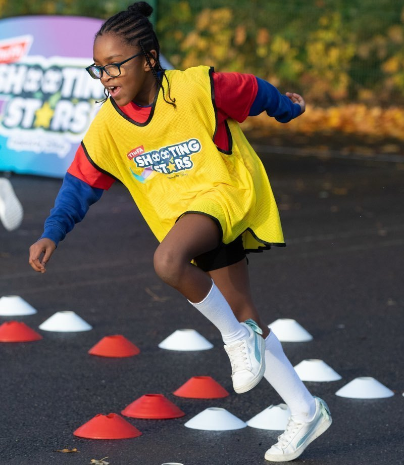 A girl in a yellow bib doing a shuttle run