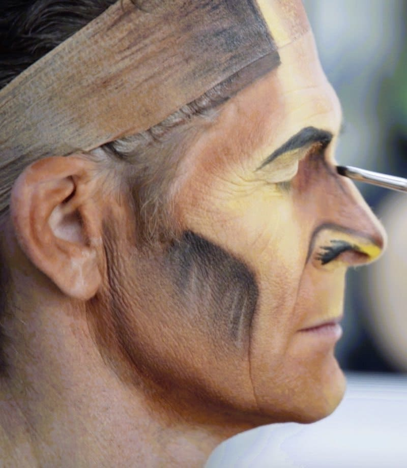 Someone applying make up on a Lion King performer