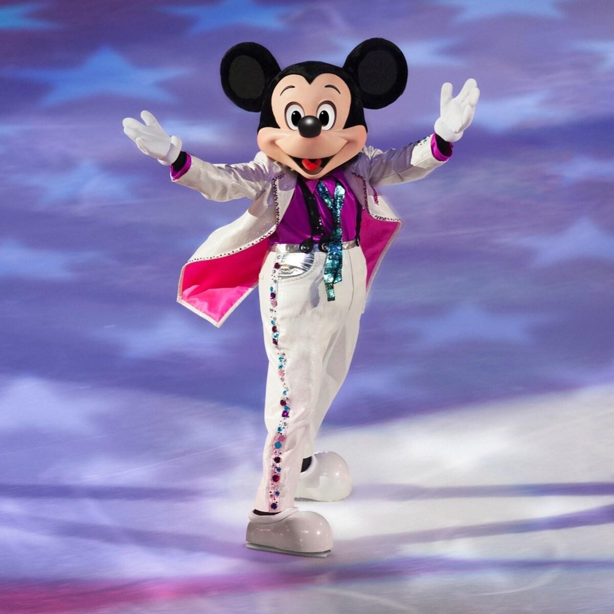 Musse Pigg i en vit kostym med armarna upp på isen