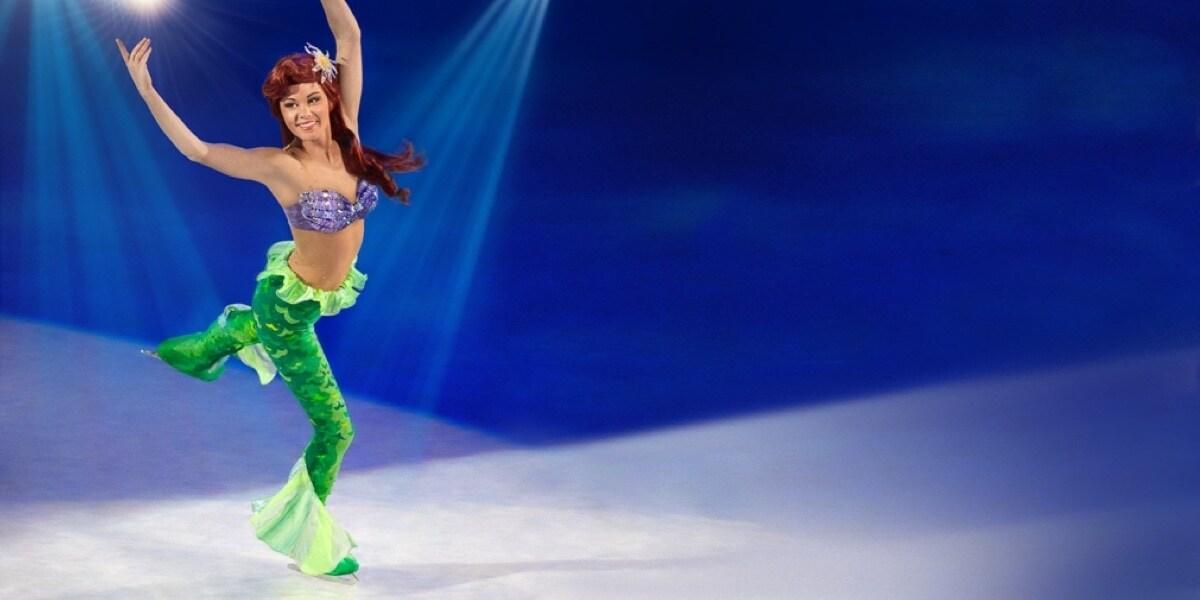 Ariel tańczy na lodzie z uniesionymi ramionami