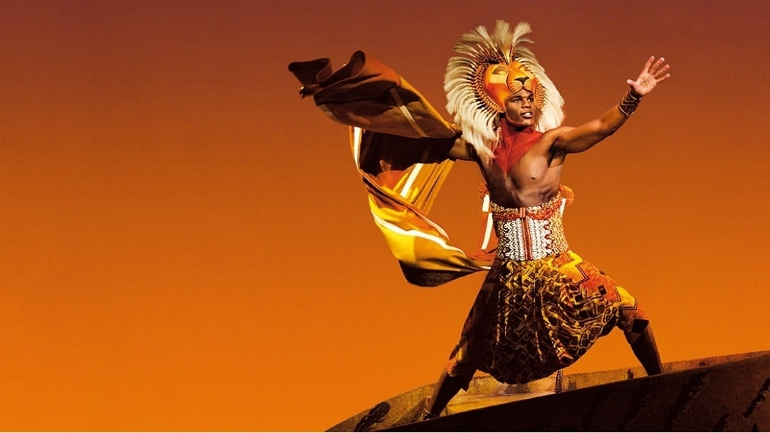 A performer dressed as Simba standing on pride rock