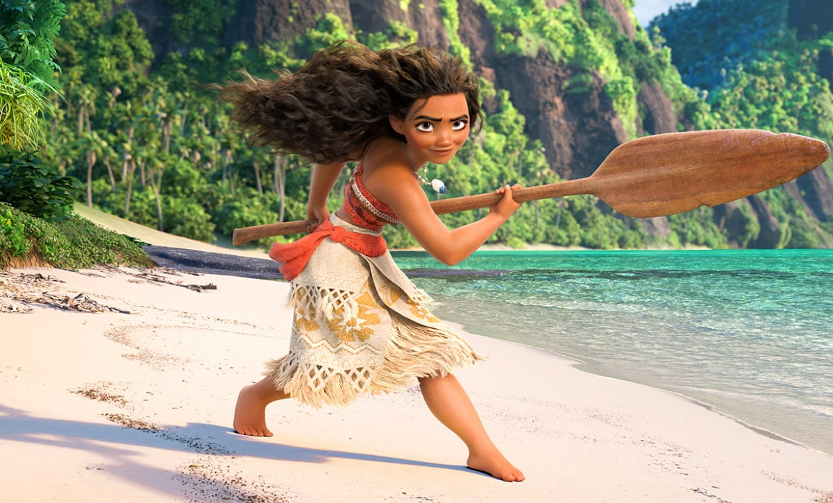 Moana standing on a beach holding a wooden oar