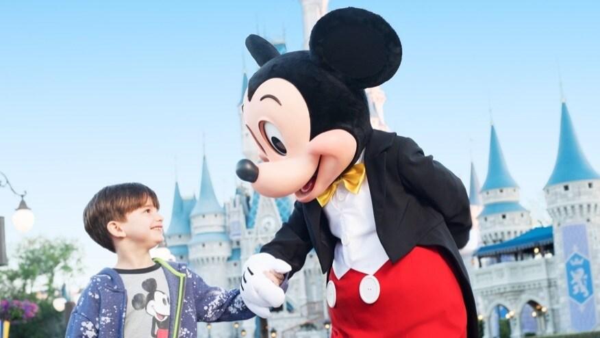 Topolino mano nella mano con un bambino a Walt Disney World