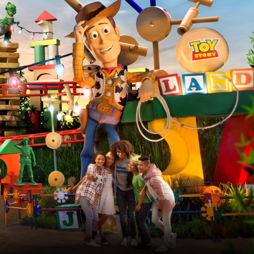 A group of friends taking a selfie in front of Woody in Toy Story Land at Walt Disney World