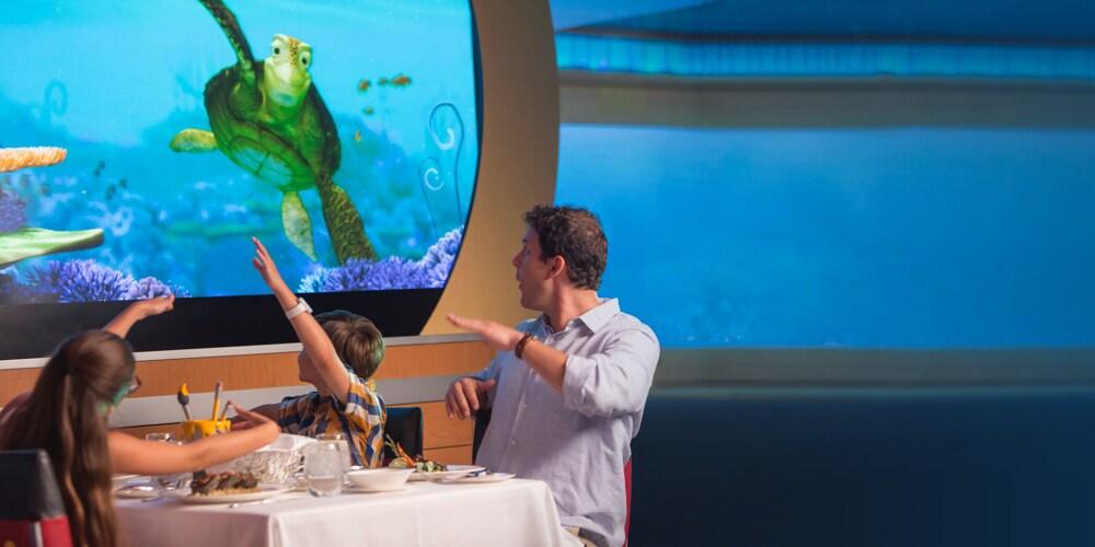 Familia sentada en una mesa señalando una gran pantalla en la que sale la tortuga Crush