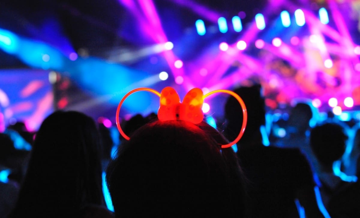 A girl wearing a light up Mickey ears headband looking at a lightshow in a Disney Park