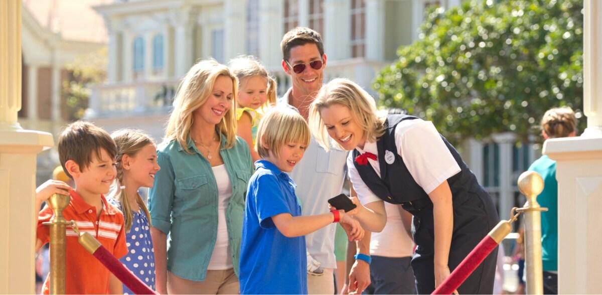 Una cola familiar mientras un miembro del reparto escanea un FastPass + en la muñeca de un niño
