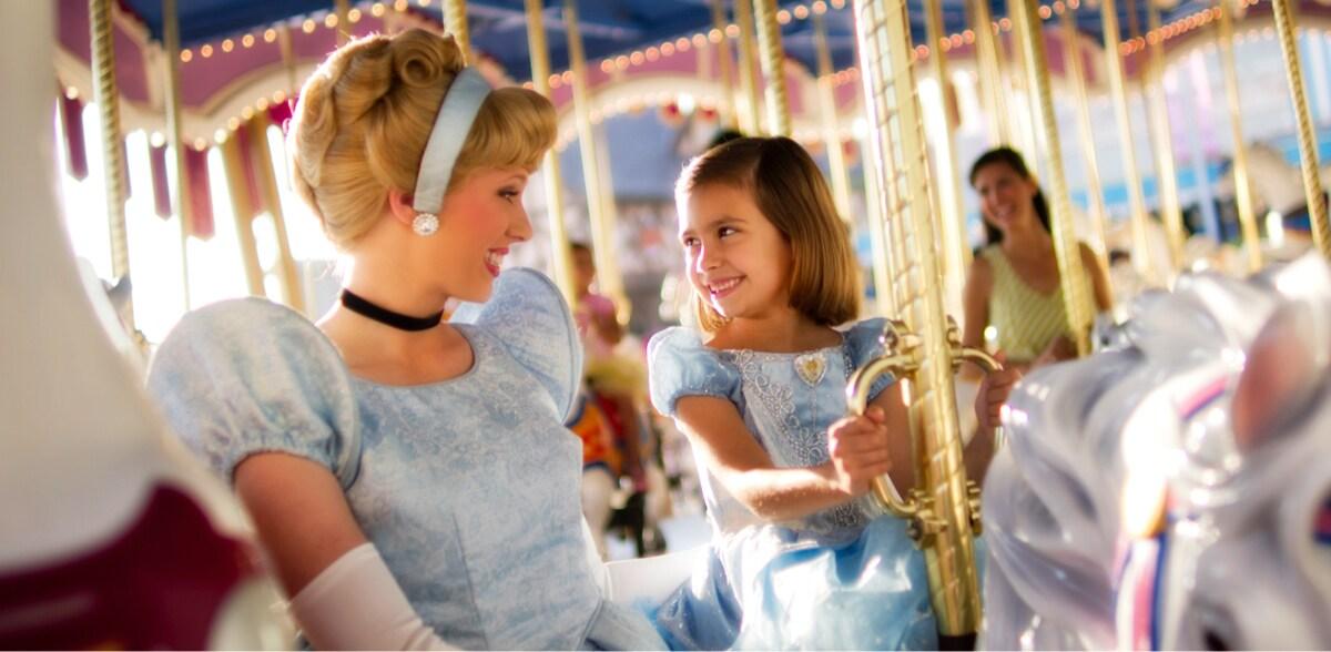 Disney Princess Cinderella with a a young guest dressed as Cinderella on Cinderella's Golden Carousel ride