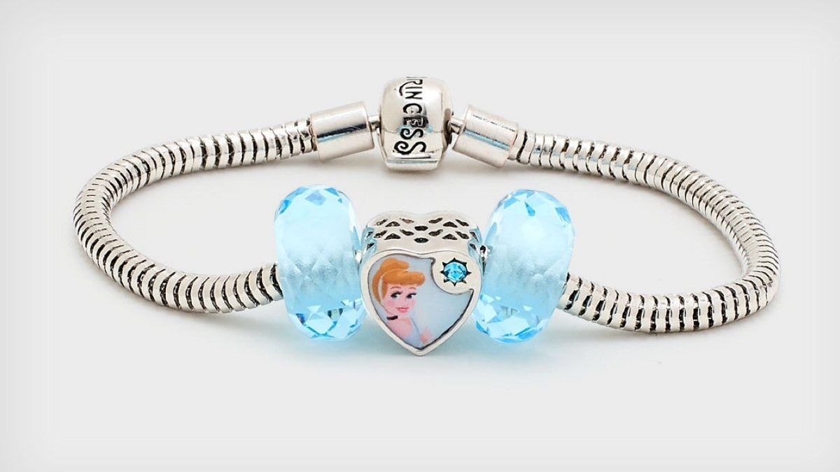 Three piece set features a heart-shaped bead with classic Cinderella character artwork, and two matching blue glass beads.