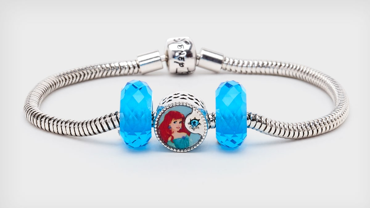 Three piece set features a heart-shaped bead with classic Aerial character artwork, and two matching blue glass beads.
