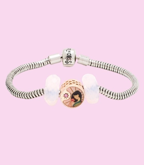 Three piece set features a circular bead with classic Mulan character artwork, and two matching glass beads.
