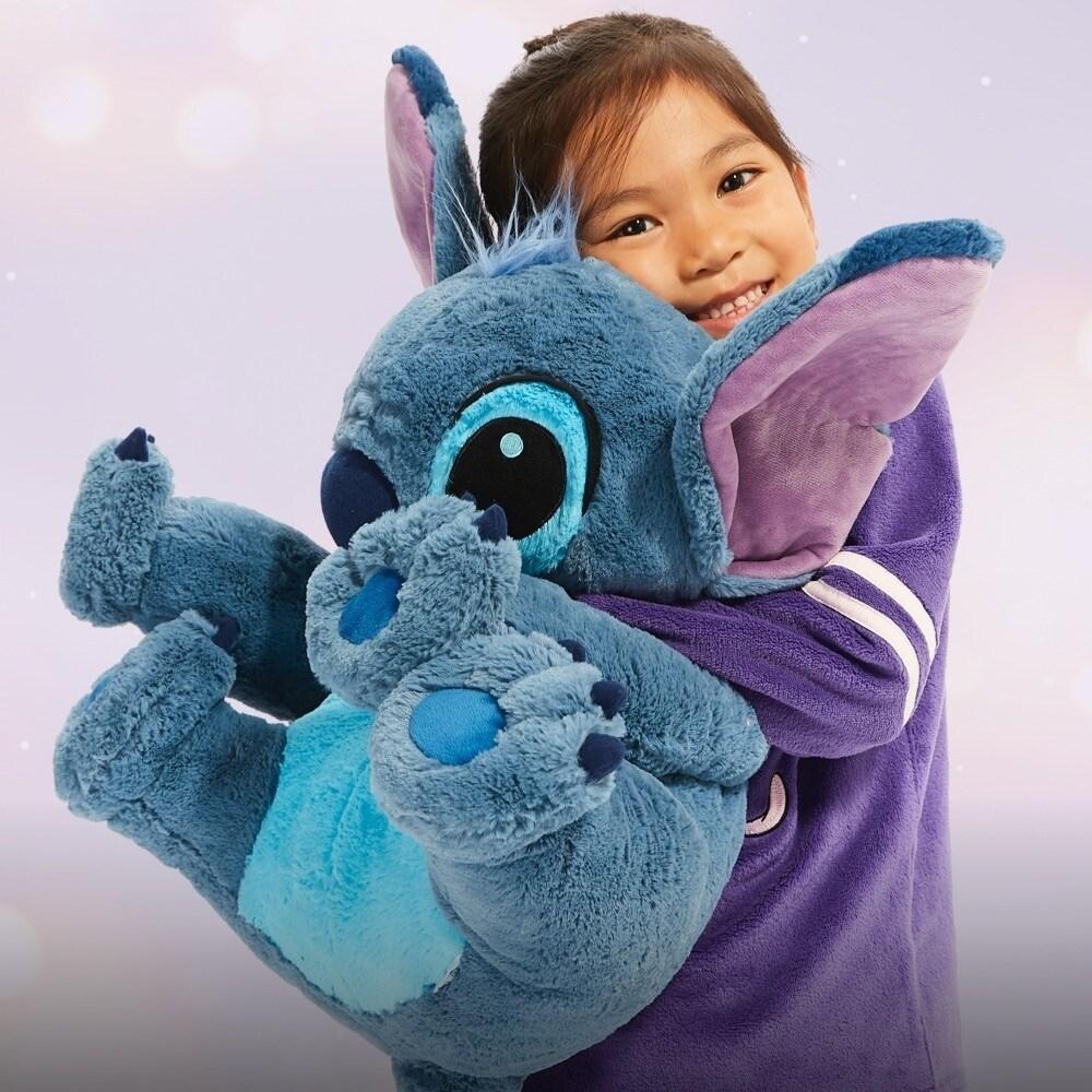 Girl hugging large Stitch soft toy