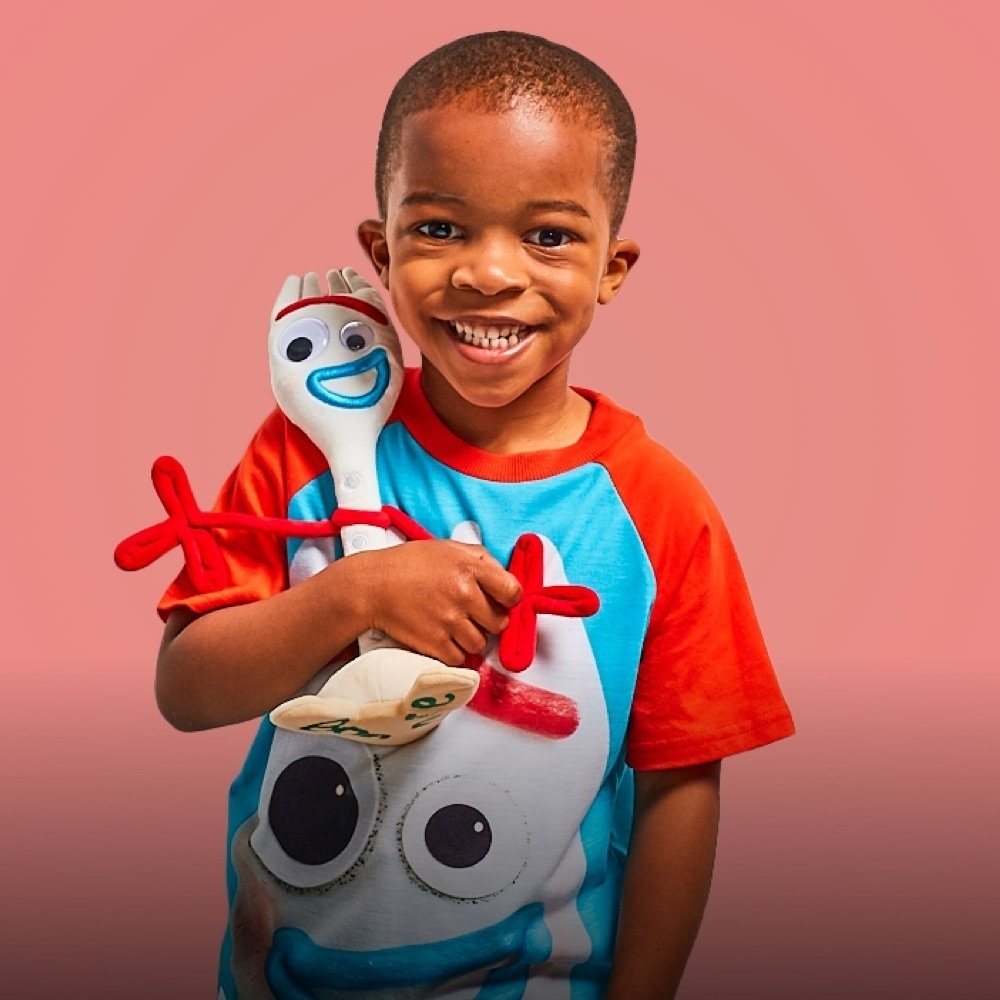 Boy hugging Forky inspired soft toy