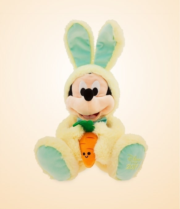 Peluches de Mickey y Minnie Easter vestidos con atuendos de conejito tendidos en un césped rodeado de huevos de Pascua