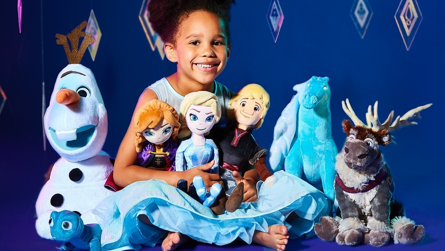 Fille portant une robe La Reine des Neiges tenant une peluche inspirée La Reine des Neiges