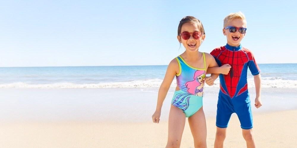 A boy and girl wearing Disney inspired swimwear