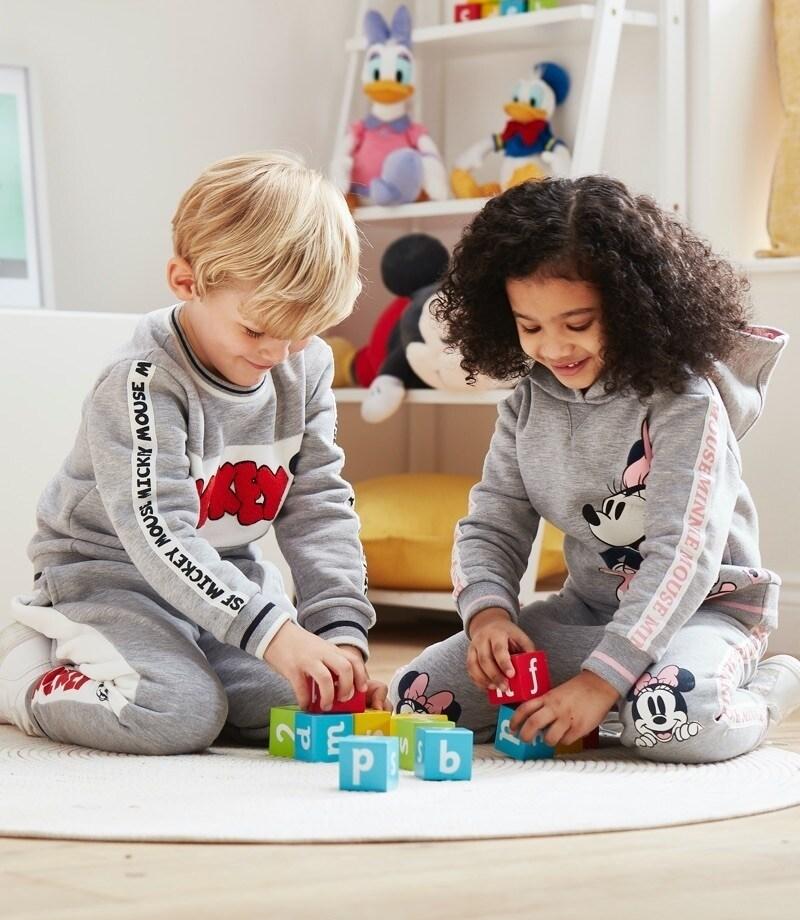 Kinder, die von Mickey und Minnie inspirierte Trainingsanzüge tragen
