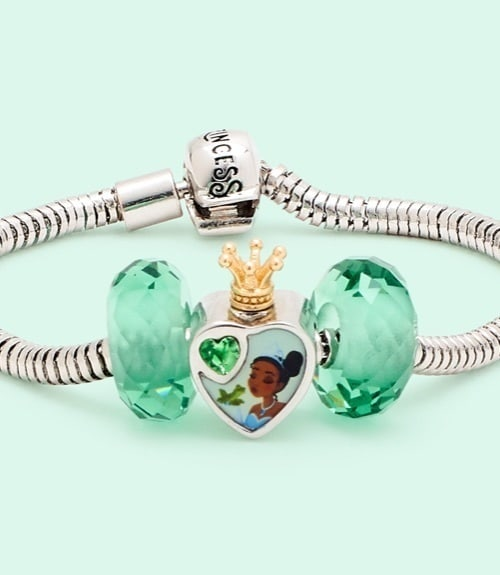 Tiana inspired charm and two beads on a silver bracelet.