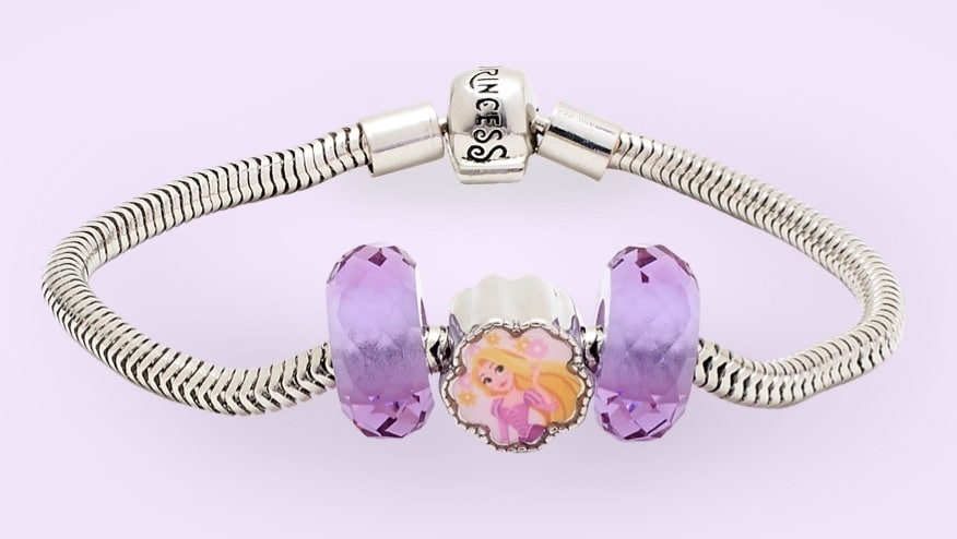 Rapunzel inspired charm and two purple beads on a silver bracelet.