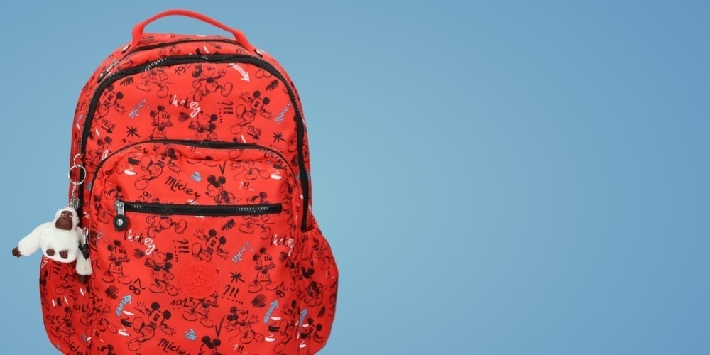 Red backpack by Kipling featuring Mickey in animated sketch-style poses.