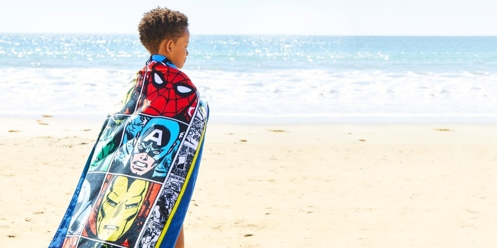 Boy holding a towel featuring designs inspired by the Hulk, Iron Man and Captain America.