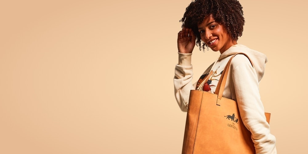 A Women carrying a tan coloured The Lion King tote bag
