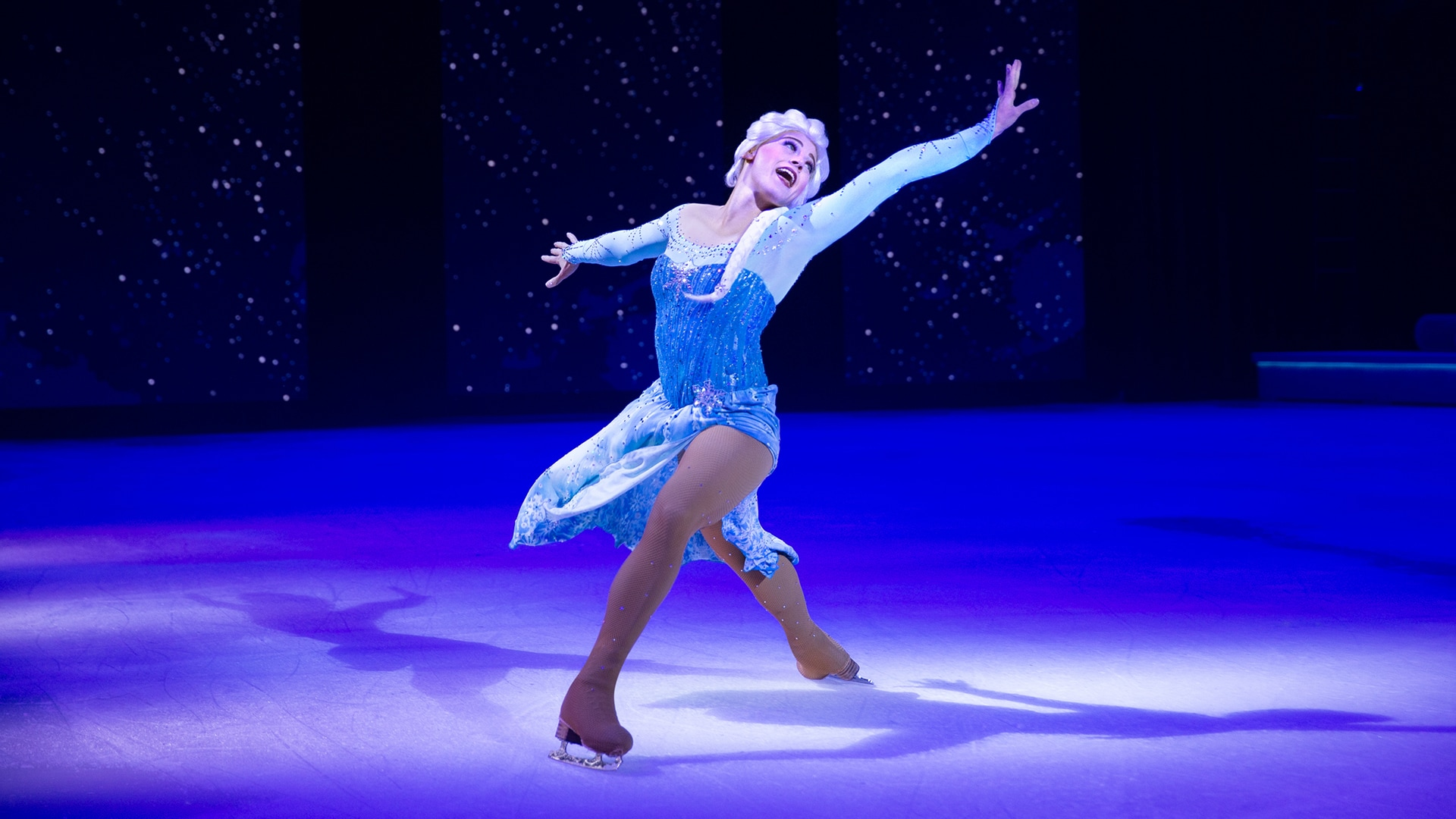 Elsa on a spotlight while singing and dancing on ice with her arms spread to the sides.