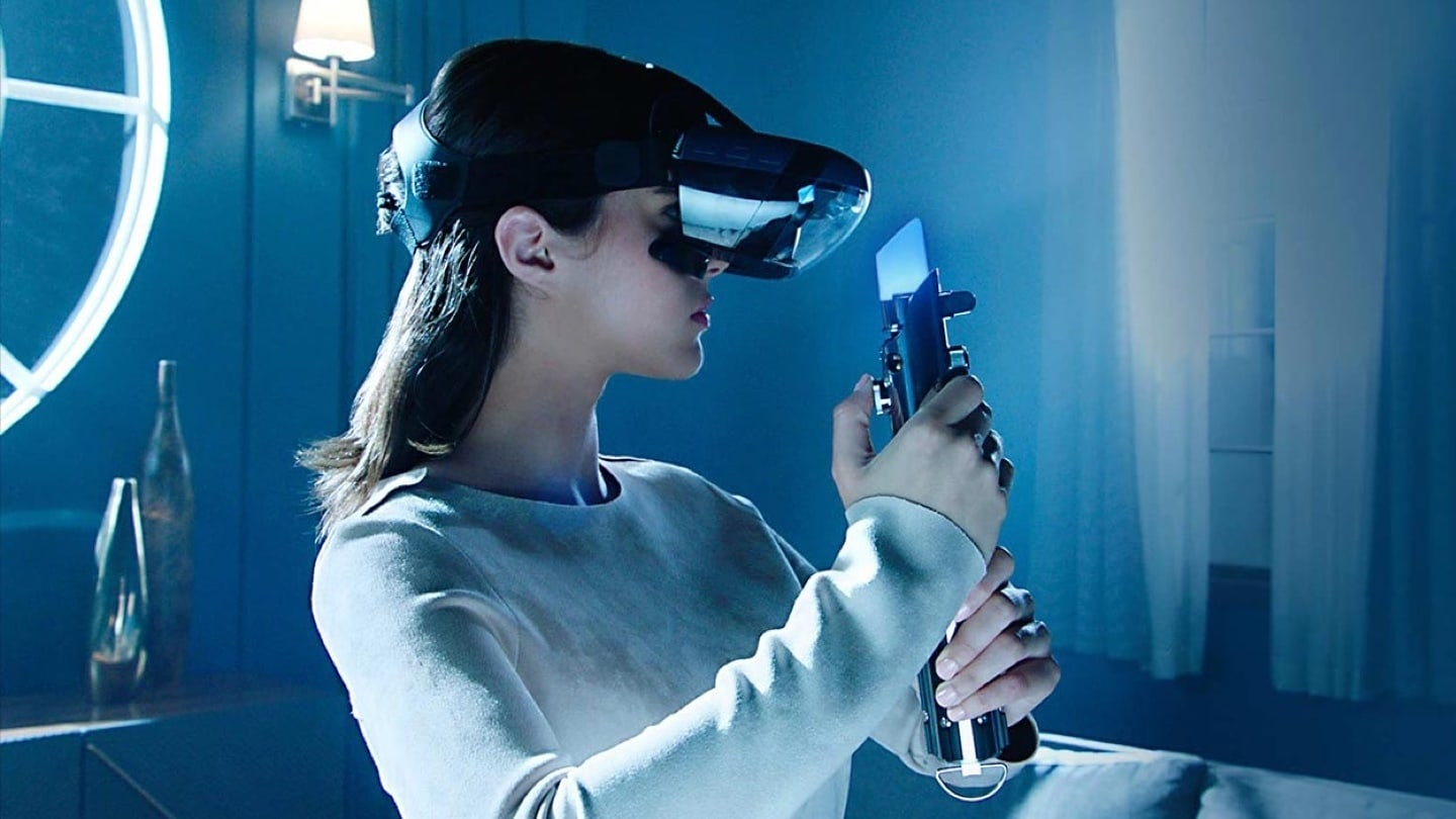 A female wearing the Mirage AR headset and holding a Lightsaber controller