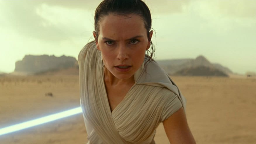 Daisy Ridley in costume as Rey holding a Lightsaber