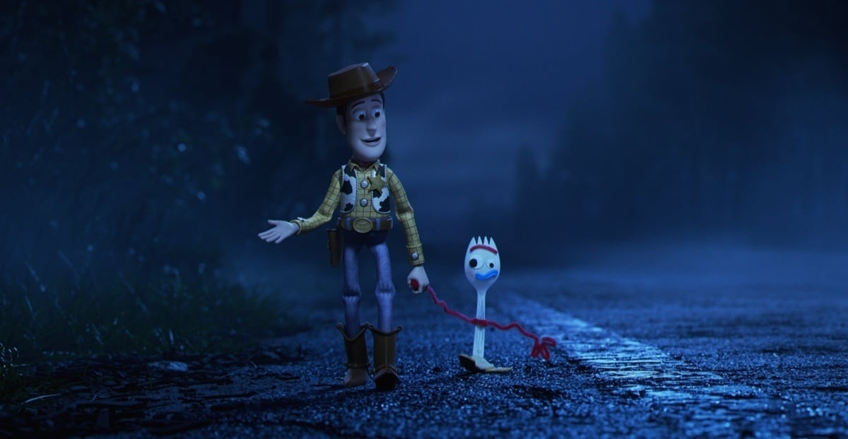 Woody and Forky holding hands whilst walking down a road.