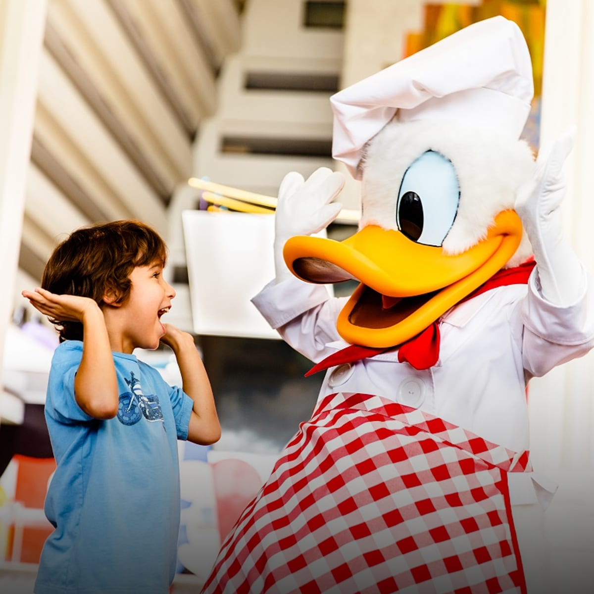 Donald Duck in a chef outfit laughing with a child