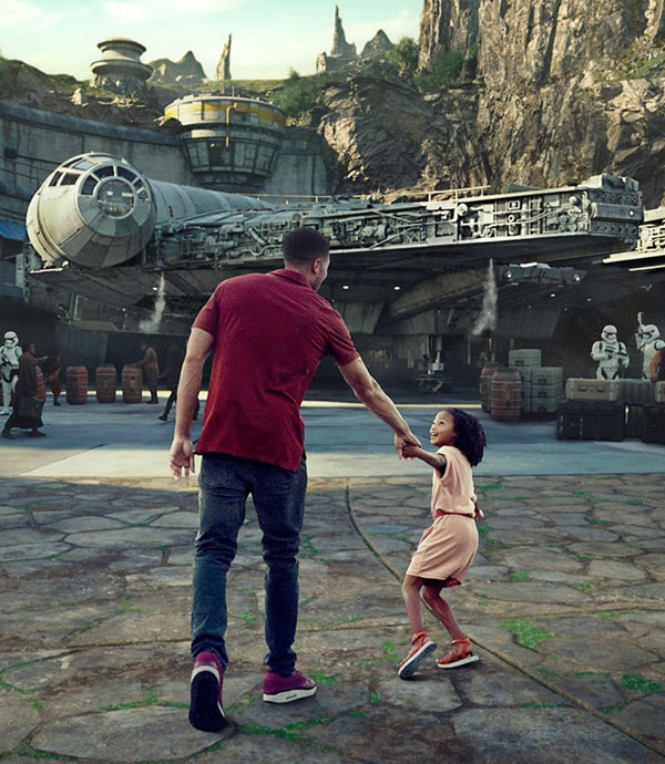 Father and daughter walking towards the Millennium Falcon