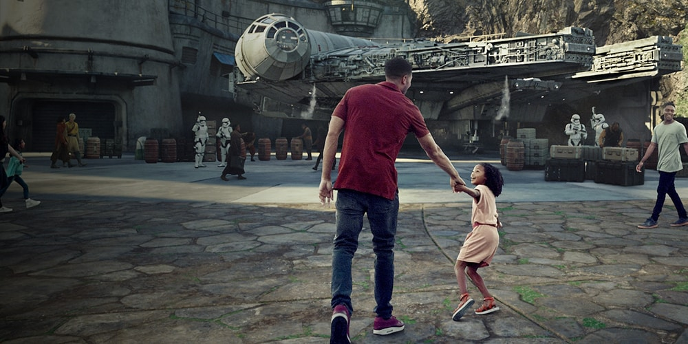 A girl pulling her father by the hand towards the Millennium Falcon